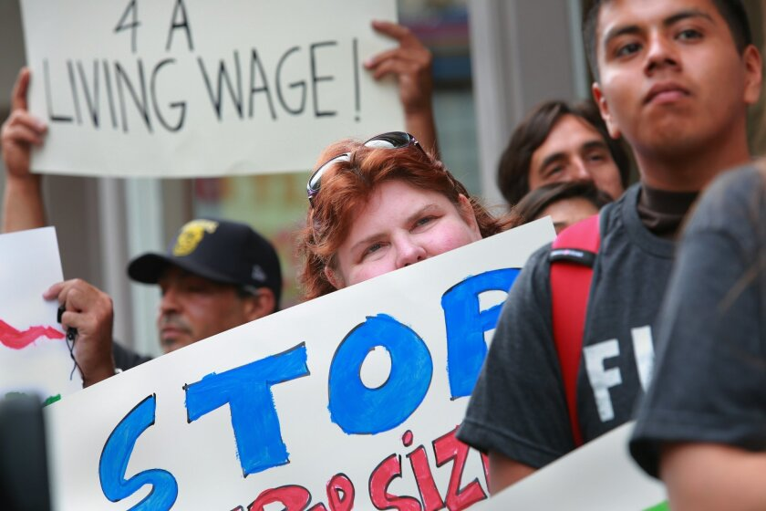 """Diane Cates holds a sign reading """"Stop Supersizing Poverty"""" while supporting a hike in the minimum wage last year outside a Wendy's in downtown San Diego. Peggy Peattie • U-T file"""