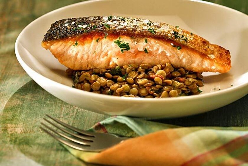 Crisp-skinned salmon on a bed of bacon-flavored lentils and dandelion greens. Recipe