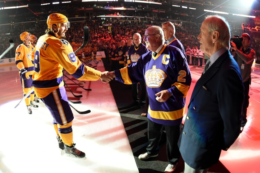 The Kings' Drew Doughty shakes hands with former Kings captain Bob Wall during a ceremony celebrating the team's 50th anniversary.