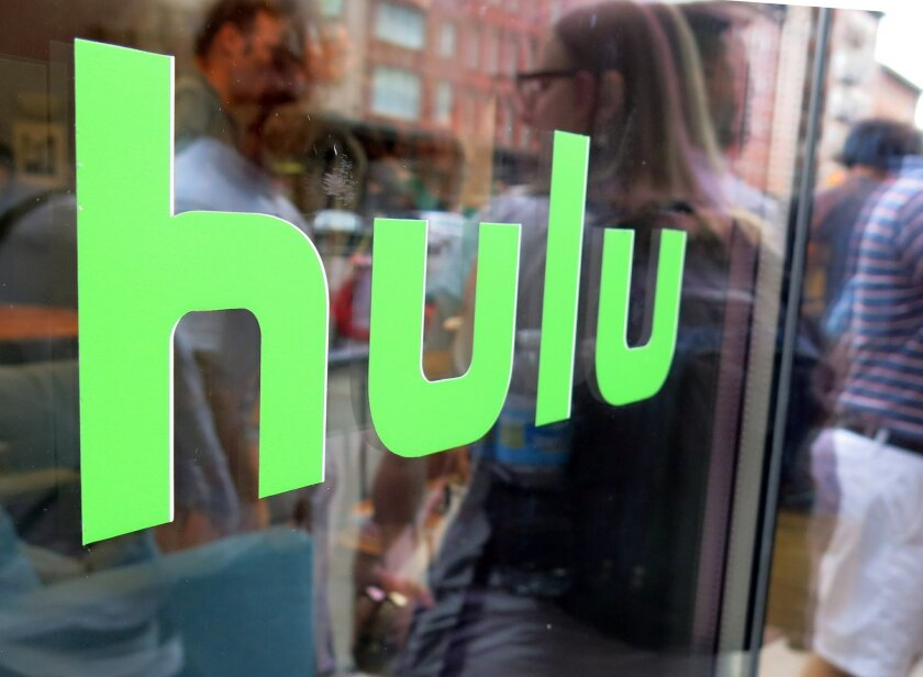 """FILE - This Saturday, June 27, 2015, file photo, shows the Hulu logo on a window at the Milk Studios space in New York, where a replica of the """"Seinfeld"""" set was on display. Some television companies are balking as more people watch shows online, and may start delaying the release of shows to strea"""