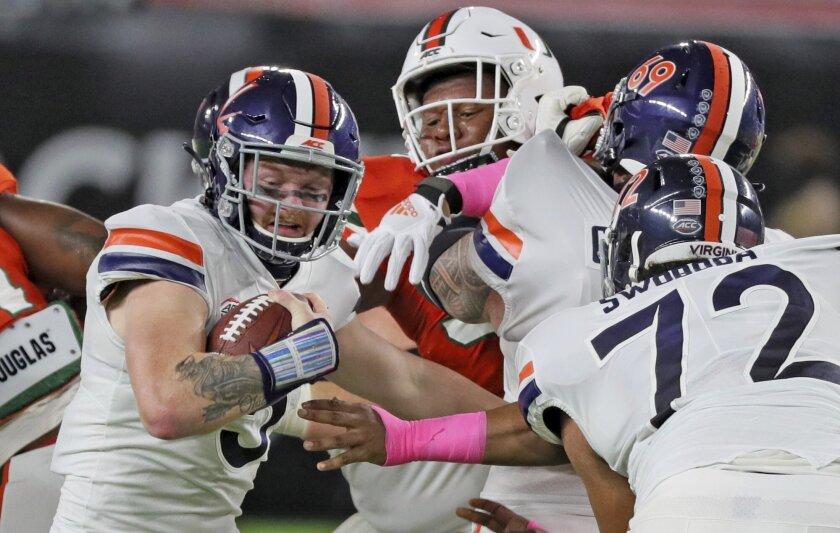 The Miami defense pressures Virginia quarterback Brennan Armstrong (5) on a keeper in the first quarter of an NCAA college football game in Miami Gardens, Fla., Saturday, Oct. 24, 2020. (Al Diaz/Miami Herald via AP)