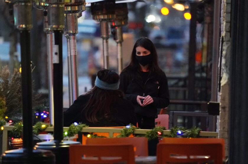 A server wears a protective mask while tending to a patron sitting in the outdoor patio of a restaurant.