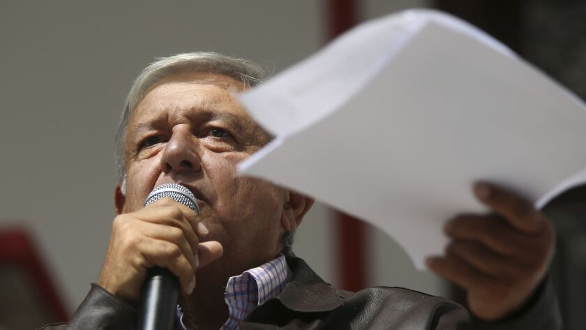 Mexico's President-elect Andres Manuel Lopez Obrador holds documents outlining the presidential sala