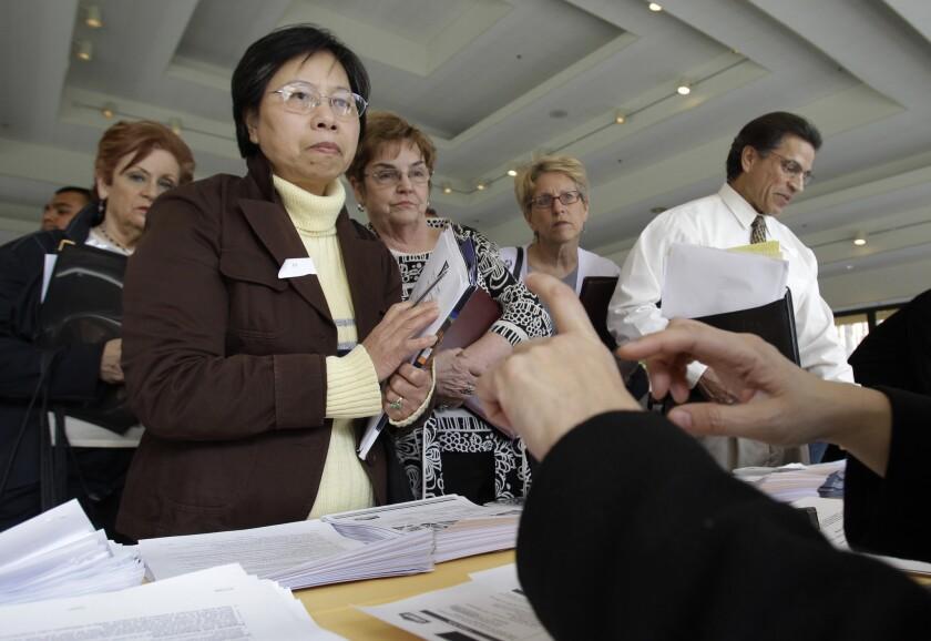 Applicants listen to a recruiter at a job fair in San Jose.