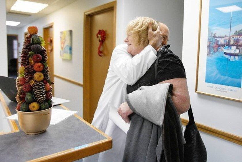Dr. Damian Folch hugs Martha Thomas, 54, after her appointment at his office in Chelmsford, Mass. Folch is among thousands of physicians in Massachusetts whose pay depends on how their patients fare.