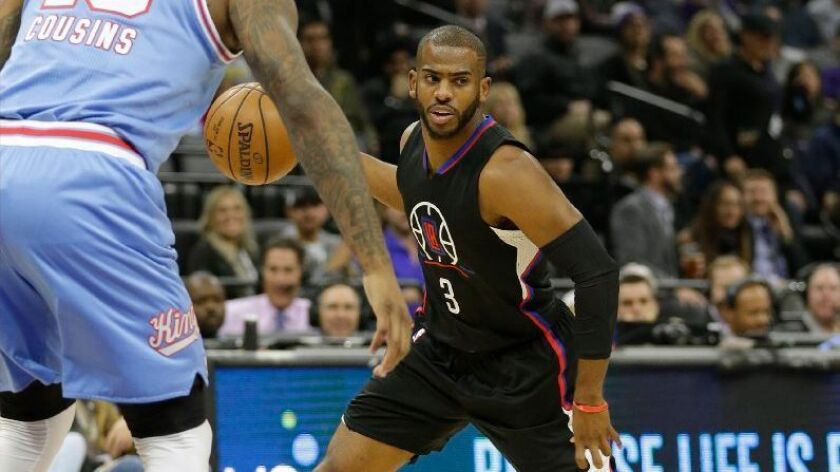 Clippers guard Chris Paul looks to pass while being defended by Kings big man DeMarcus Cousins during a game in Sacramento on Jan. 6.