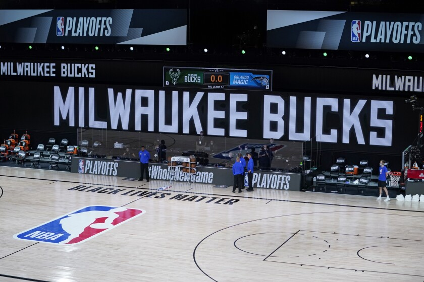 Officials stand beside an empty court at an NBA playoff game between the Milwaukee Bucks and the Orlando Magic on  Aug. 26.