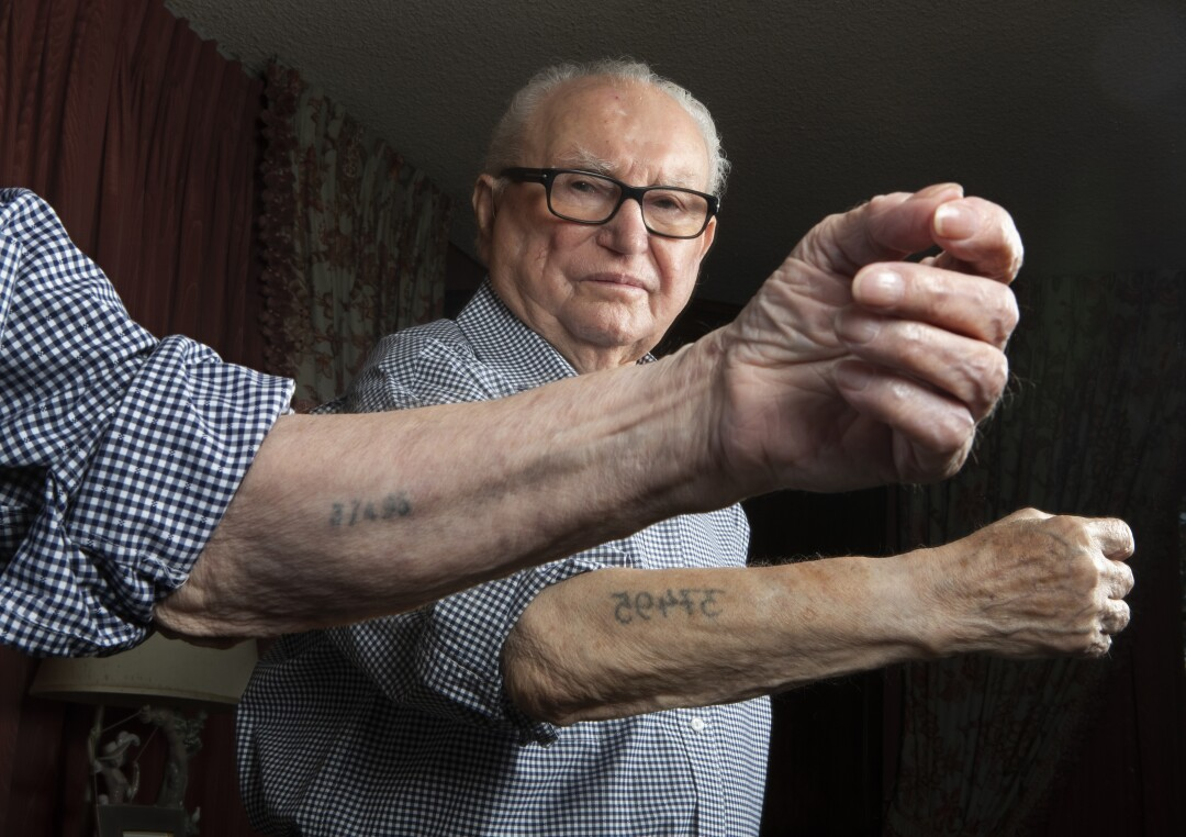 Hakman shows his prisoner number tattooed on both sides of his left arm. He received the smaller one, in the foreground, when he first arrived at Auschwitz in 1942, and the larger one the next day at Birkenau.