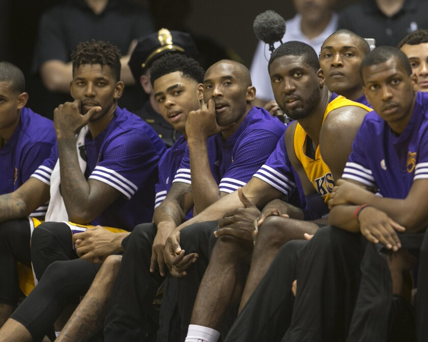 Lakers guard Kobe Bryant, center, sits on the bench with teammates during the fourth quarter of Sunday's preseason opener in Honolulu.