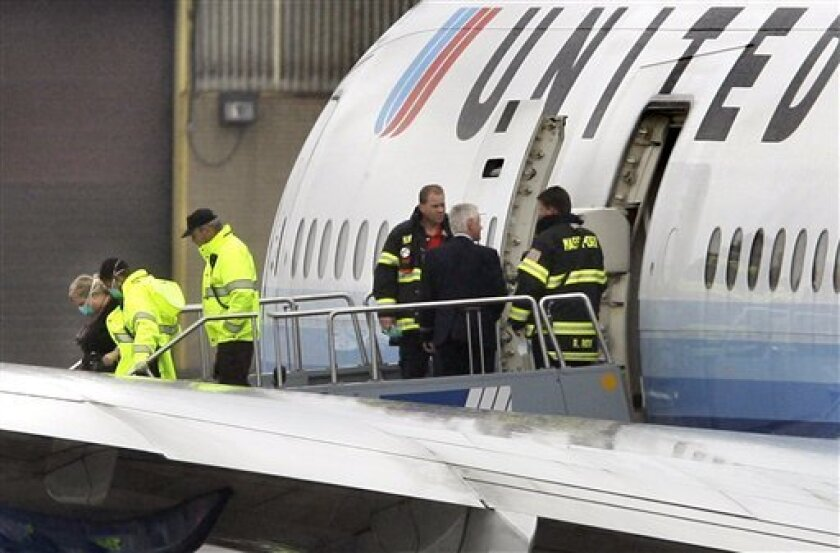 "A female passenger, far left, wears a mask as she is accompanied down the steps of a United Airlines jetliner to a waiting ambulance at Logan international Airport in Boston Friday, May 1, 2009. The flight originating from Munich, Germany to Washington, D.C. had been diverted to Boston because the passenger complained of ""flu-like symptoms"" according to airport spokesman Phil Orlandella. (AP Photo/Elise Amendola)"