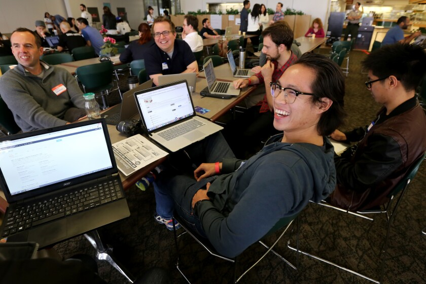"""A group at L.A.'s """"hackathon"""" share a light moment while brainstorming on Day 1 of the two-day event, which aims to use the skills of the technology sector to develop tools to improve residents' lives."""