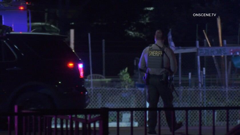 A sheriff's deputy stands outside a vehicle with emergency lights flashing after a gunman shot an Escondido police officer.