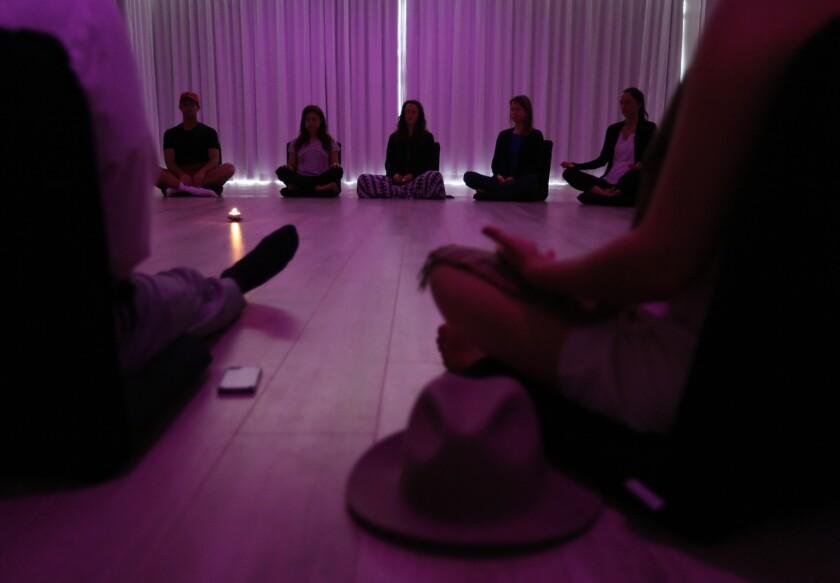 Participants meditate during a class at Unplug, a new meditation studio.