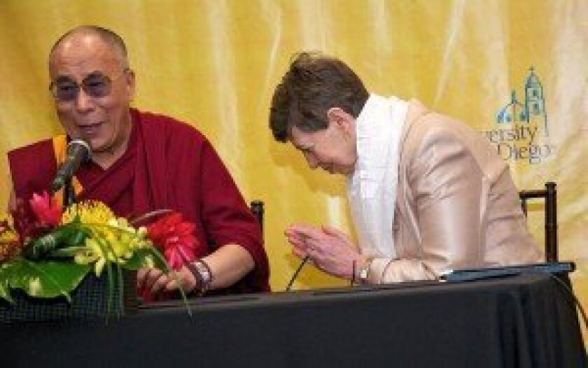UC San Diego Chancellor Marye Anne Fox showed customary respect to the Dalai Lama after he presented her with a Tibetan scarf.  Photo: Carol Sonstein