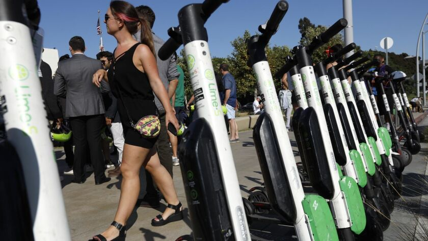 SANTA MONICA, CA - AUGUST 14, 2018 - A woman walks past a row of parked Lime and Bird scooters durin