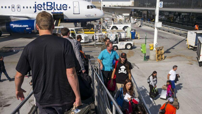 Passengers disembark from a JetBlue Airways plane at Long Beach Airport.