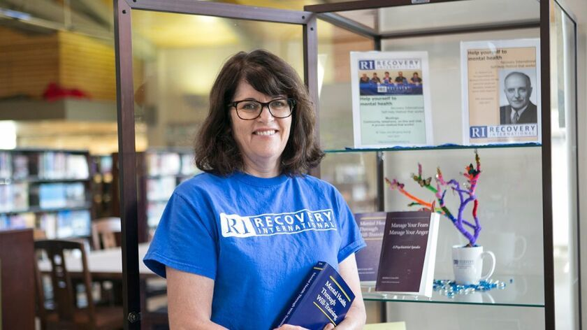 Recovery International San Diego volunteer Judi Bakke at the Rancho San Diego Library, where the group has a display devoted to its programs.