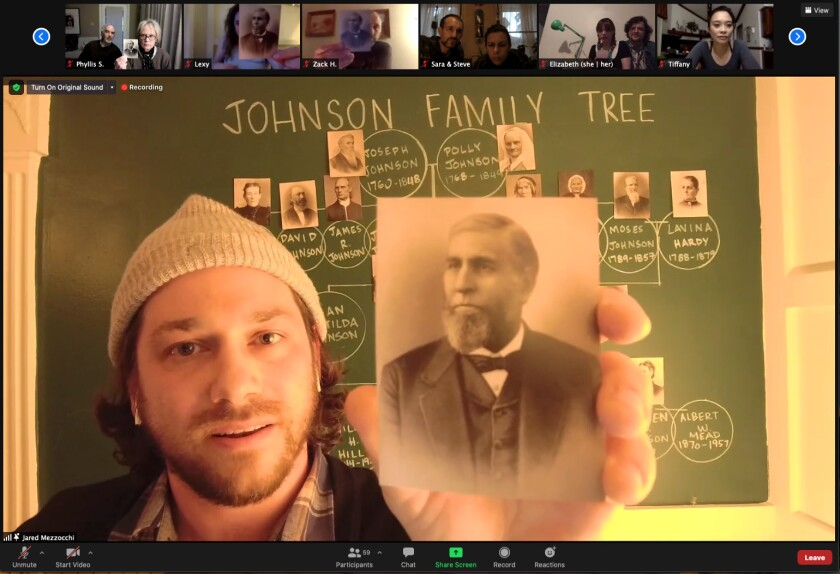 A man holds a black and white photo of his ancestor in front of a chalkboard depicting a family tree