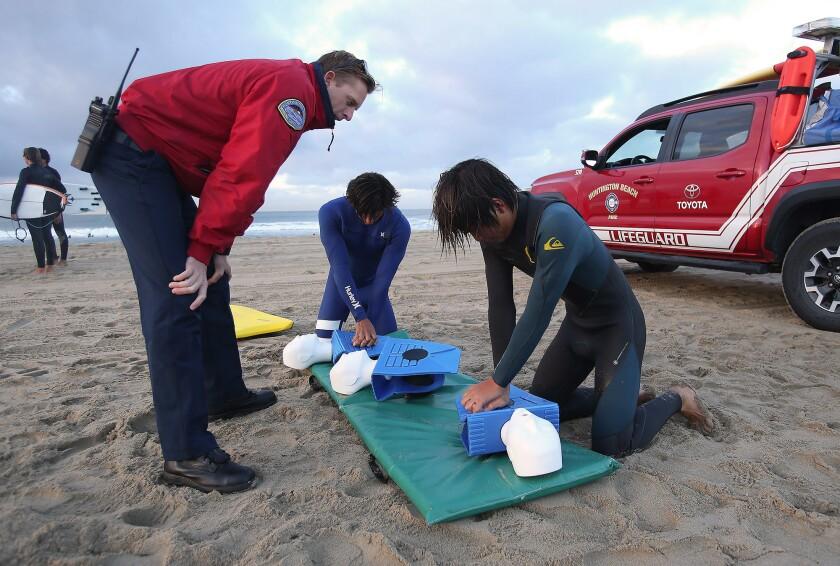 Huntington Beach marine safety officer Sterling Foxcroft teaches Huntington Beach High School students Sage Guinaleo, center, and Keanu Igarashi proper chest compression methods during a session Wednesday to train members of the school surf team in lifesaving techniques.