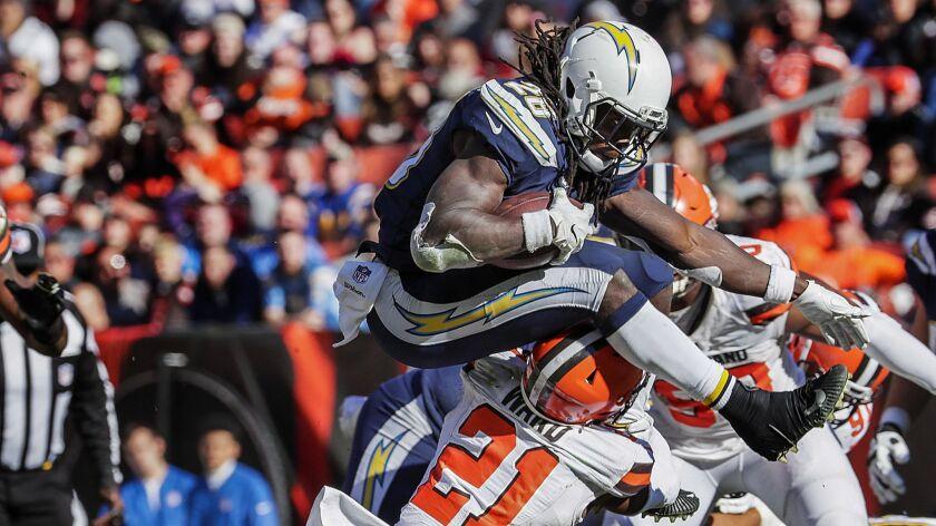 Chargers running back Melvin Gordon leaps over Browns defensive back Denzel Ward.
