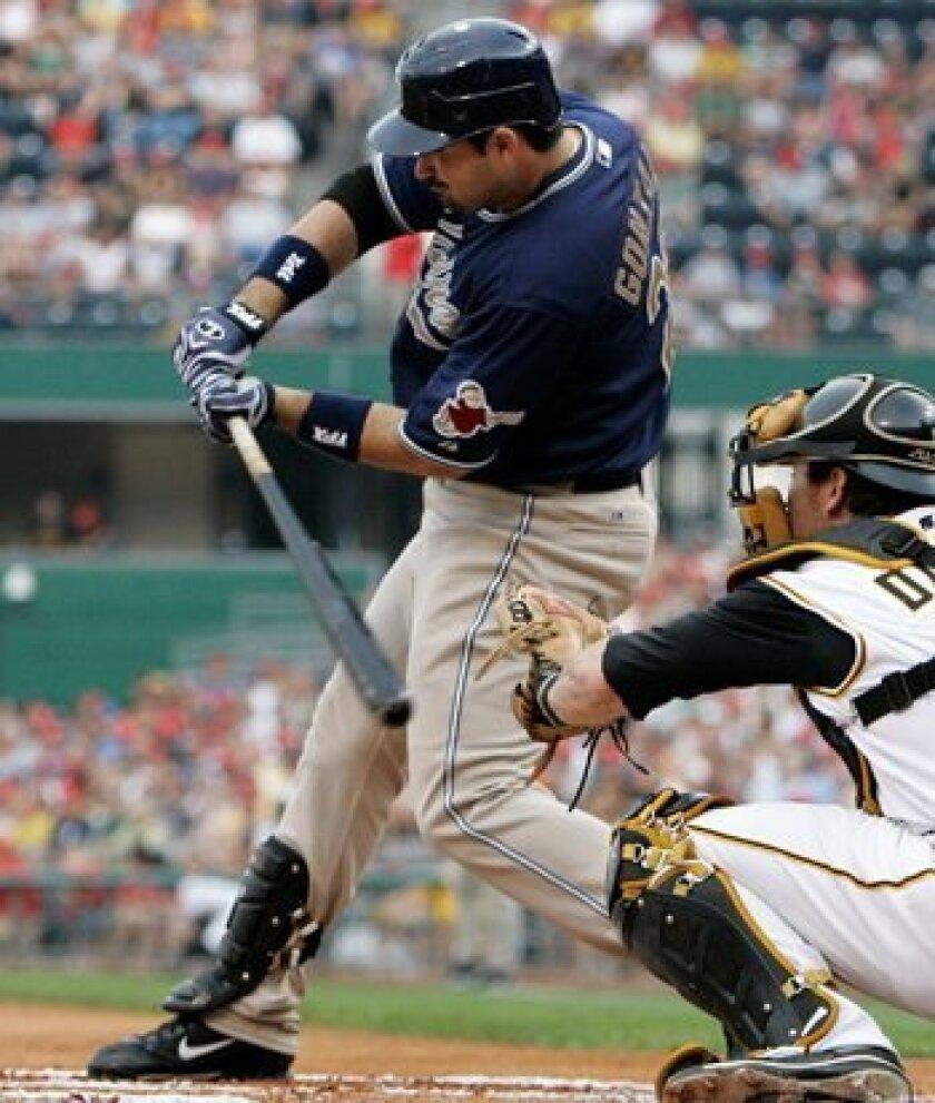 Padres slugger Adrian Gonzalez, left, hits a first-inning, three-run home run off Pittsburgh Pirates pitcher John Van Benschoten as Pirates catcher Ryan Doumit watches in Pittsburgh Saturday.