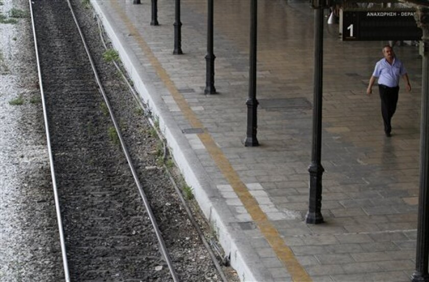A man walks by empty rail tracks at a railway station during a train strike in Athens on Thursday, June 10, 2010. Greek railway workers went on a 24-hour strike Thursday to protest government plans to overhaul the loss-making company, cut unprofitable lines and partially privatize the train operating company Trenose. The cash-strapped Greek government says the state-owned railways lose up to 1 billion euros a year, and have accrued debts of around 10 billion euros. (AP Photo/Kostas Tsironis)