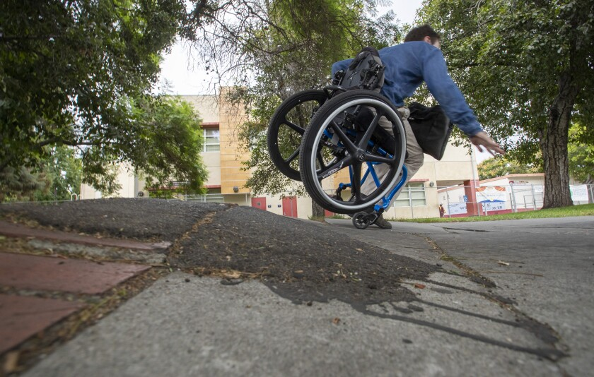 David Radcliff, who has cerebral palsy, tumbles over a section of broken sidewalk on Jefferson Boulevard across from USC.