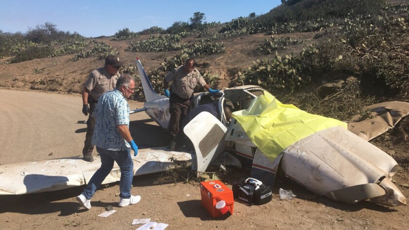 Los Angeles County Sheriff's deputies and firefighters assist three people who were involved in a single-engine plane crash on Catalina Island.