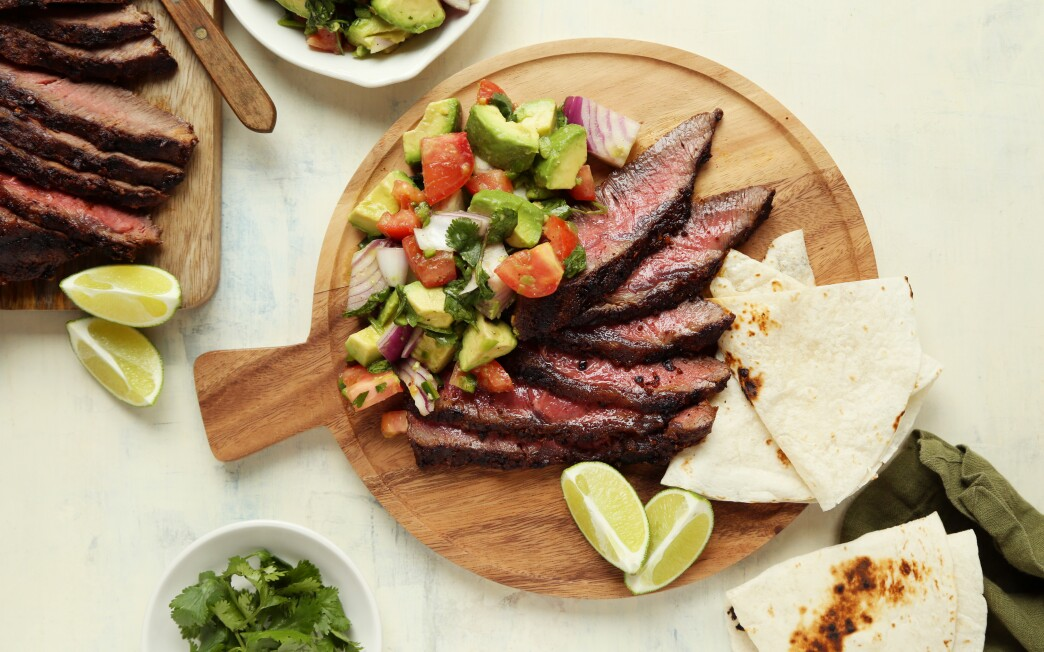 Large chunks of avocado and veggies act as a salad to super-flavorful steak seasoned with taco spices.
