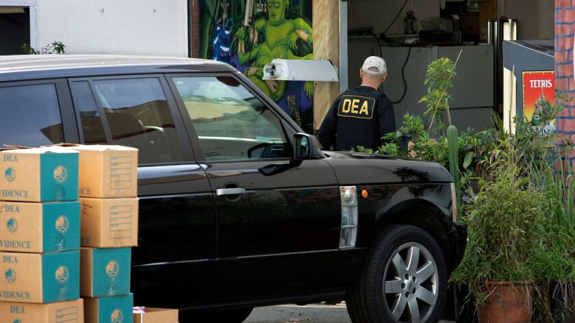 Federal agents and Los Angeles police officers raid a Culver City medical marijuana dispensary, Organica Collective, in 2010.