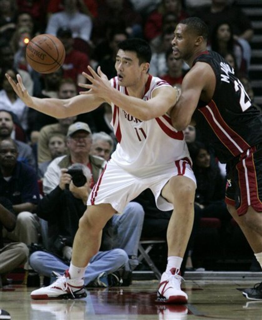 Houston Rockets' Yao Ming (11) from China tries to maintain control of the ball against Miami Heat's Jamaal Magloire (21) during the first half of a NBA basketball game Saturday, Jan. 17, 2009 in Houston. (AP Photo/Pat Sullivan)