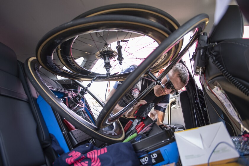 20190514. Education First team mechanic Tom Hopper lifts up the stack of spare wheels in the back s