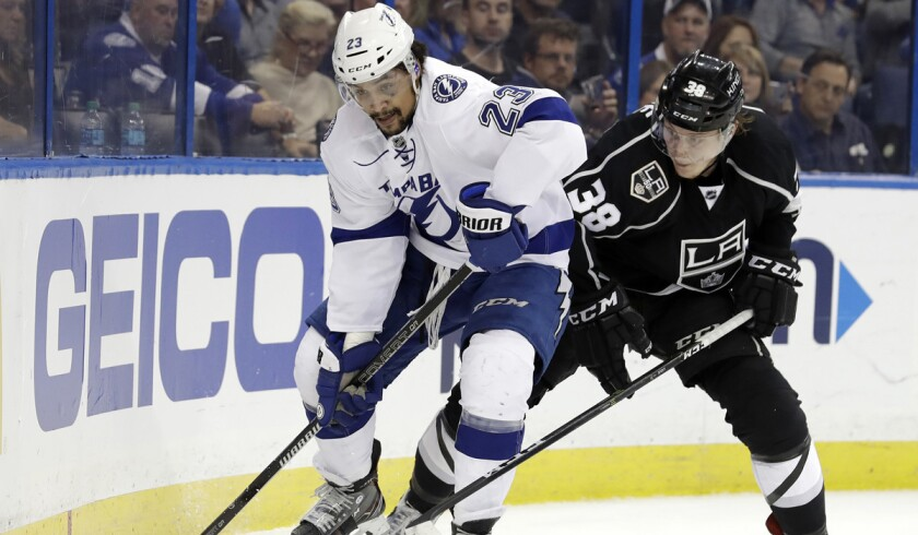 Tampa Bay Lightning right wing J.T. Brown, left, moves the puck ahead of Kings defenseman Paul LaDue during the second period.