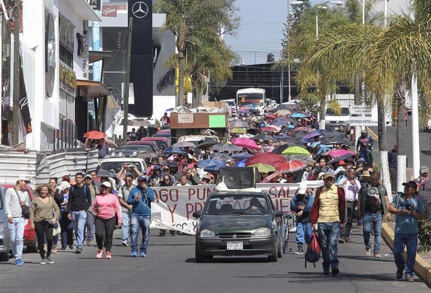 Maestros de educación básica marchan este jueves, por las principales avenidas de la ciudad de Morelia en el estado de Michoacán (México). Los maestros de educación básica alargaron hoy el bloqueo del sistema ferroviario del occidental estado mexicano de Michoacán a la espera de que el gobierno local reciba recursos federales para cubrir sus salarios y poner fin a la protesta que comenzó el pasado 7 de enero. EFE