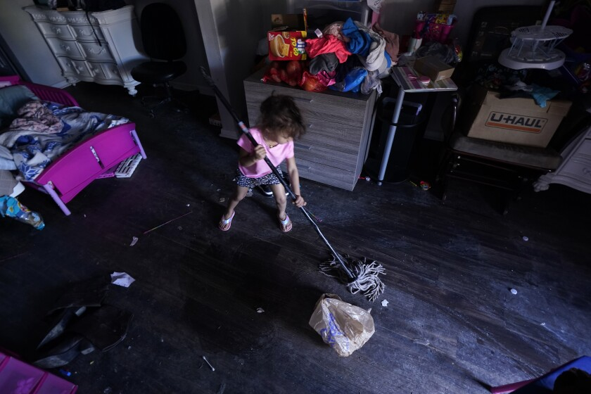 Raella Mills, 3, plays mop-up at her home in Dallas.