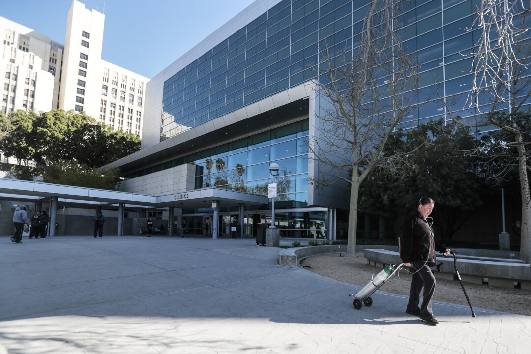 A person with a cane and oxygen tank walks outside a hospital building