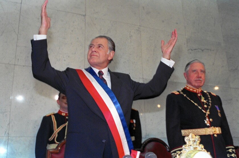 Patricio Aylwin, left, speaks after receiving the presidential sash at inaugural ceremonies in Santiago, Chile, in March of 1990 as outgoing President Augosto Pinochet looks on.