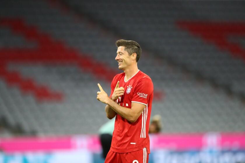 Bayern's Robert Lewandowski, celebrates after scoring a goal with a penalty kick, during the German Bundesliga soccer match between FC Bayern Munich and Schalke 04 in Munich, Germany, Friday, Sept. 18, 2020. (AP Photo/Matthias Schrader)