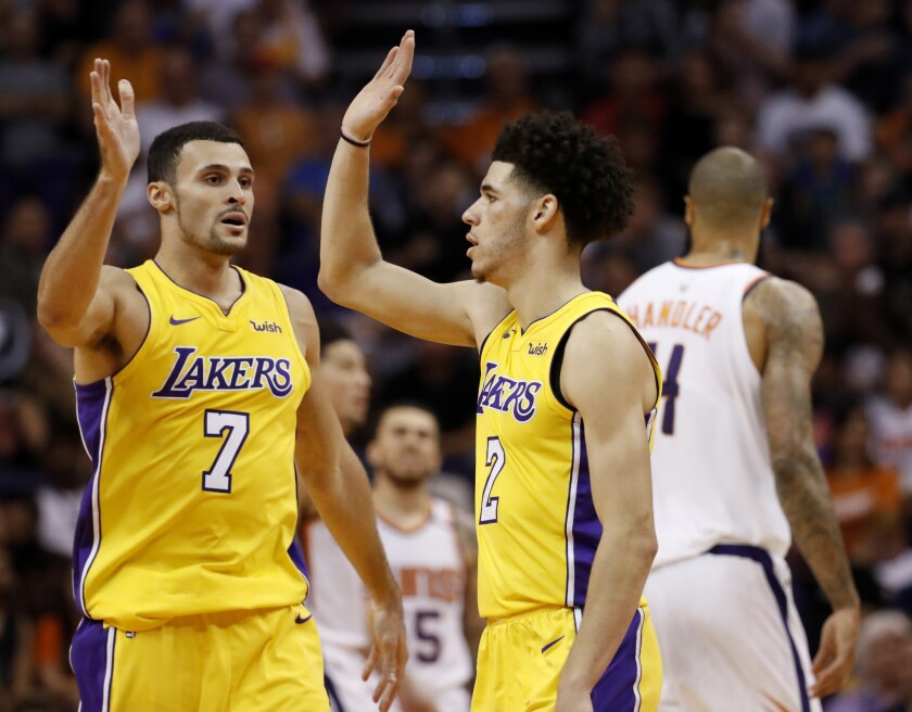 Lakers guard Lonzo Ball (2) and forward Larry Nance Jr. (7) had plenty to celebrate near the end of their game against the Suns on Oct. 20.