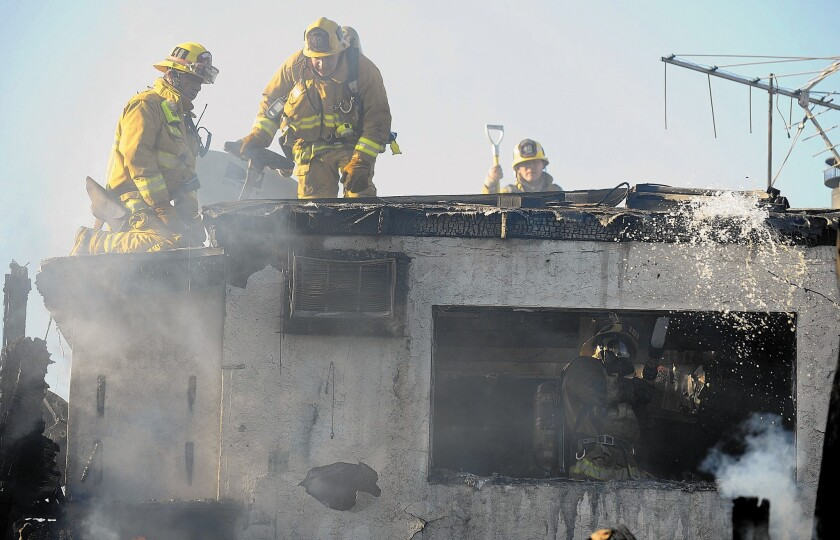 Firefighters battle a house fire in San Pedro in April. A string of lawsuits alleging bias in the department is costing the city millions of dollars.
