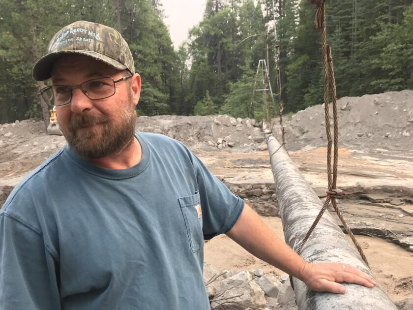 Richie Fesler stands outdoors, his hand on a pipeline and tall pine trees in the background.