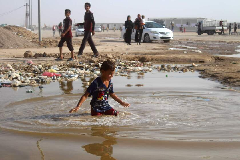A displaced Iraqi boy plays in a puddle of water at a camp in Amiriyah al-Fallouja on June 22, 2016.