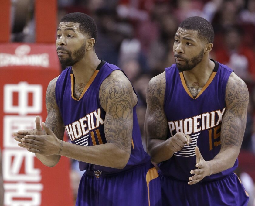 FILE - In this Dec. 6, 2014, file photo, Phoenix Suns Markieff Morris (11) and Marcus Morris (15) talk to a referee in the second half of an NBA basketball game against the Houston Rockets, in Houston. The saga of the Morris twins and the Phoenix Suns has come to an end. The trade of Markeef Morris