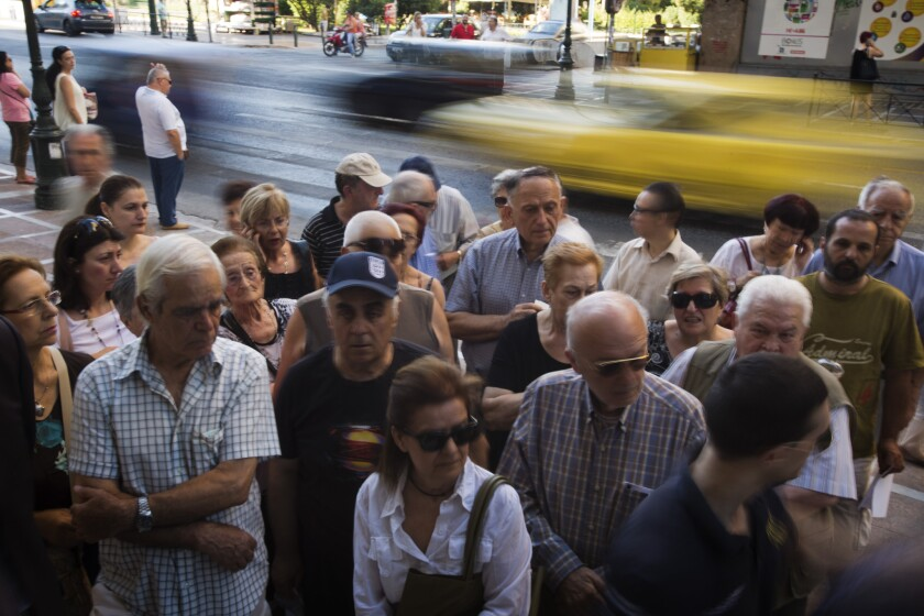 Pensioners wait outside the main gate of the national bank of Greece in Athens on July 9 to withdraw money; the maximum allowed is about $132.