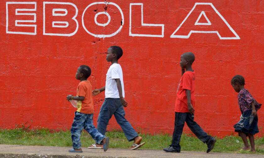 Children walk past an Ebola slogan painted on a wall in the Liberian capital, Monrovia, in August 2014.