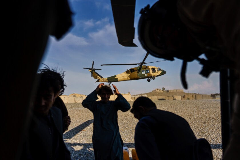 Silhouetted people appear far in front of a descending helicopter.