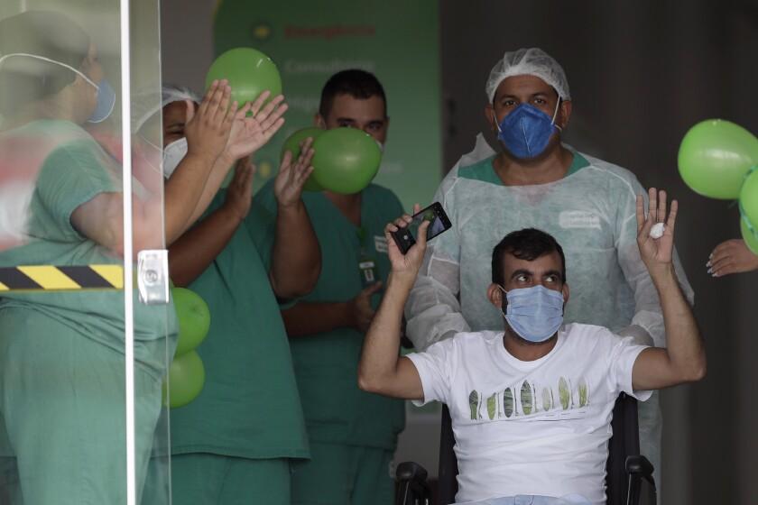 Wellington Bernardo dos Santos, de 46 años, agradece a los trabajadores de salud luego de ser dado de alta del hospital de Luziania, un suburbio de Brasilia, el jueves 25 de febrero de 2021, luego de haberse contagiado del coronavirus. (AP Foto/Eraldo Peres)
