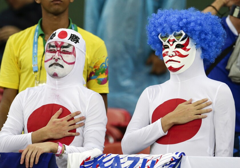 Japanese fans listen to their nation's national anthem before a World Cup soccer match between Ivory Coast and Japan on June 14 at the Arena Pernambuco in Recife, Brazil.