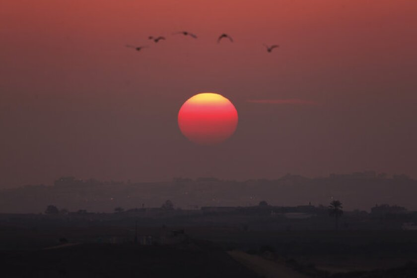 Birds fly over the central Gaza Strip as the sun sets, as seen from a hill at the Israeli town of Sderot.