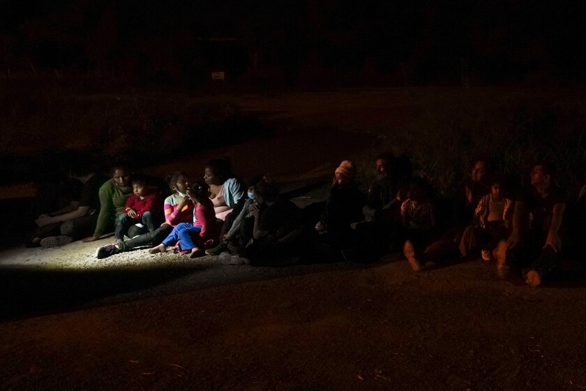 Migrants mainly from Honduras and Nicaragua sit in line